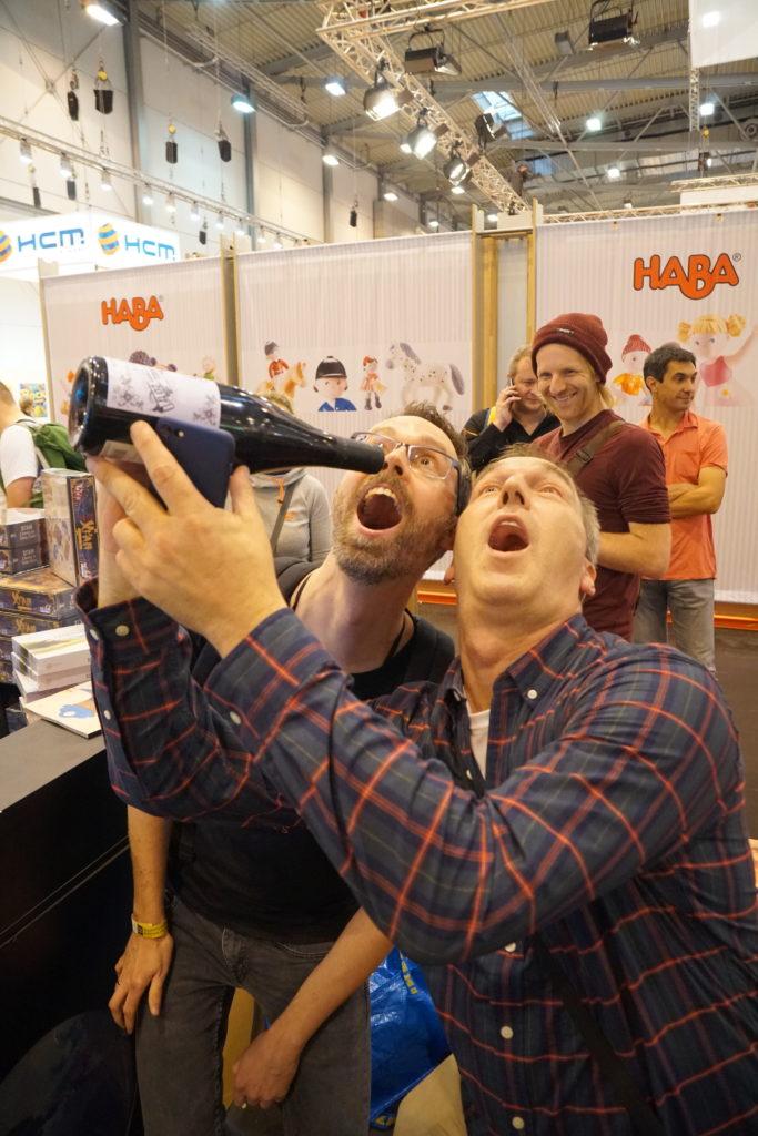 Le Spiel d'Essen c'est aussi l'occasion pour nous de remettre notre trophée du Vin d'jeu d'l'année (une bouteille de bon vin avec l'étiquette du Vin d'jeu d'l'année qu'on peut déguster par après) à l'heureux loréat. Malheureusement, Jamey, l'auteur de Scythe, ne s'est pas déplacé à Essen. Nous avons donc remis notre trophée à Morten, l'auteur de la version solo de Scythe et Stefan de Matagot. Félicitations à eux!