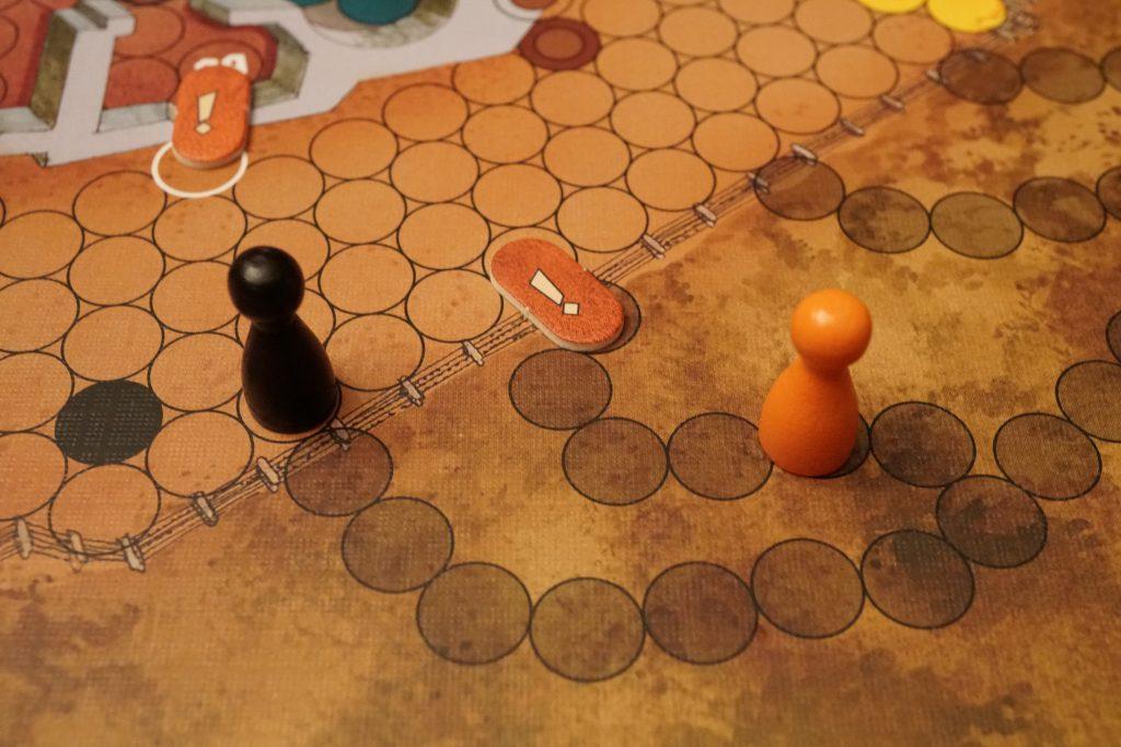 Hop, le prisonnier orange vient de tenter une évasion en lançant une corde du toit du bâtiment vers la cours extérieure (point d'exclamation en haut à gauche de la photo) puis en courant à travers la court extérieure en en coupant le fil barbelé (second point d'esclamation au centre de la photo) et en avançant de 4 cases en dehors de l'enceinte de Colditz. Le garde Allemand noir devra, sur son prochain jet de dés (il lance 2 dés), faire 8 ou plus pour rattraper le prisonnier orange qui a pris un certain risque... Mais il faut en prendre si on veut y arriver!
